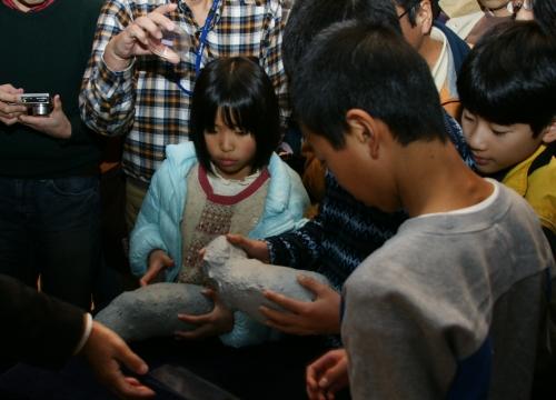 訪れた人たちは「イトカワ」の模型を手にしたり,写真に収めたり。