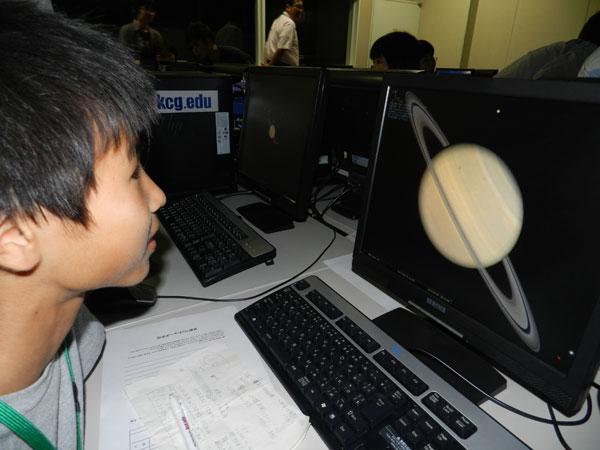 専用ソフトを使ってパソコン上で天体観測。参加した小学生は,画面に土星が現れ興奮気味。