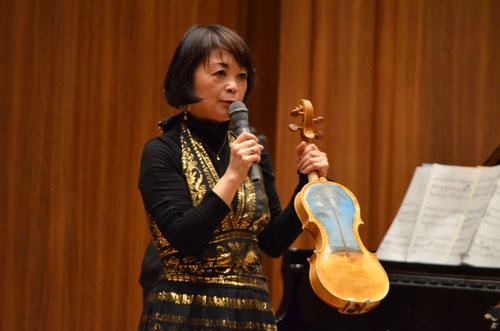 がれきとなった流木から製作したヴァイオリンを披露する中澤きみ子さん。裏面には東日本大震災による津波に耐え,被災地の人たちの支えとなってきた陸前高田市の「奇跡の一本松」が描かれています
