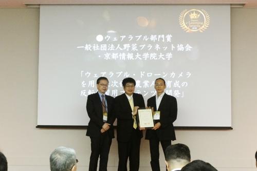 「第12回日本e-Learning大賞」でウェアラブル部門賞を受賞し表彰を受けた江見圭司准教授(中央)=2015年10月28日,東京千代田区のソラシティ カンファレンスセンター
